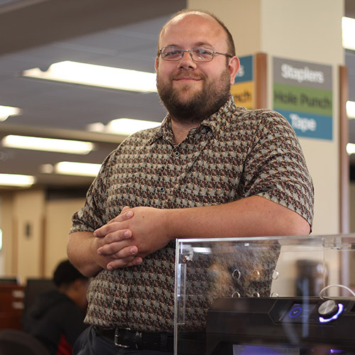 Professor and Educational Technology Specialist, Josh Moon next to a 3D printer.